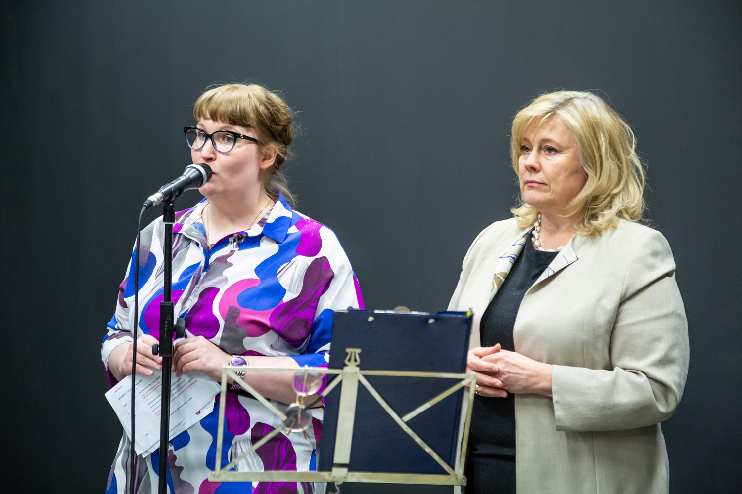 Project Coordinator and Director of Culture stand side by side in front of a microphone