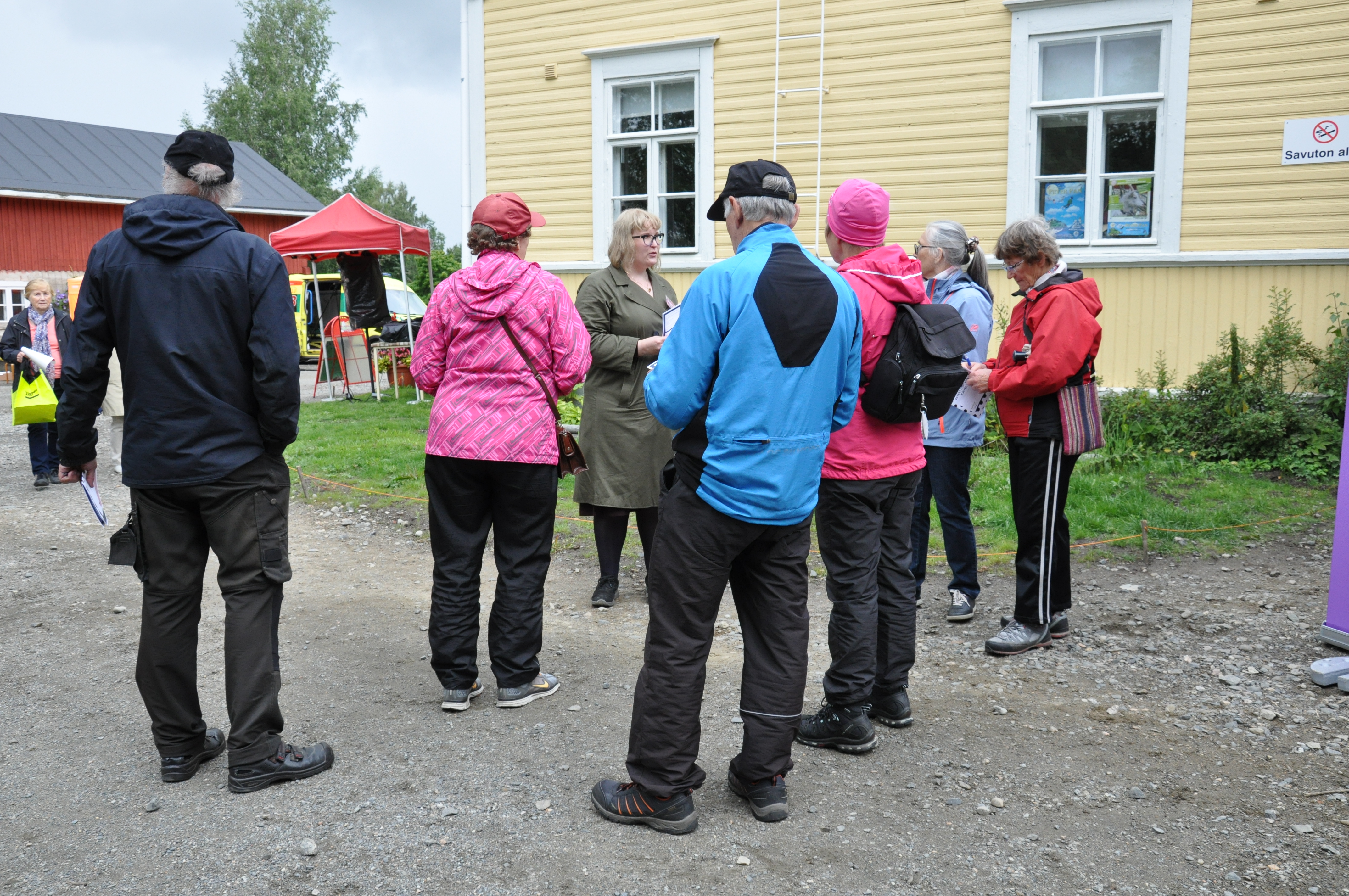 Photograph of the project coordinator speaking to a group of six people taking part in the accessibility walk
