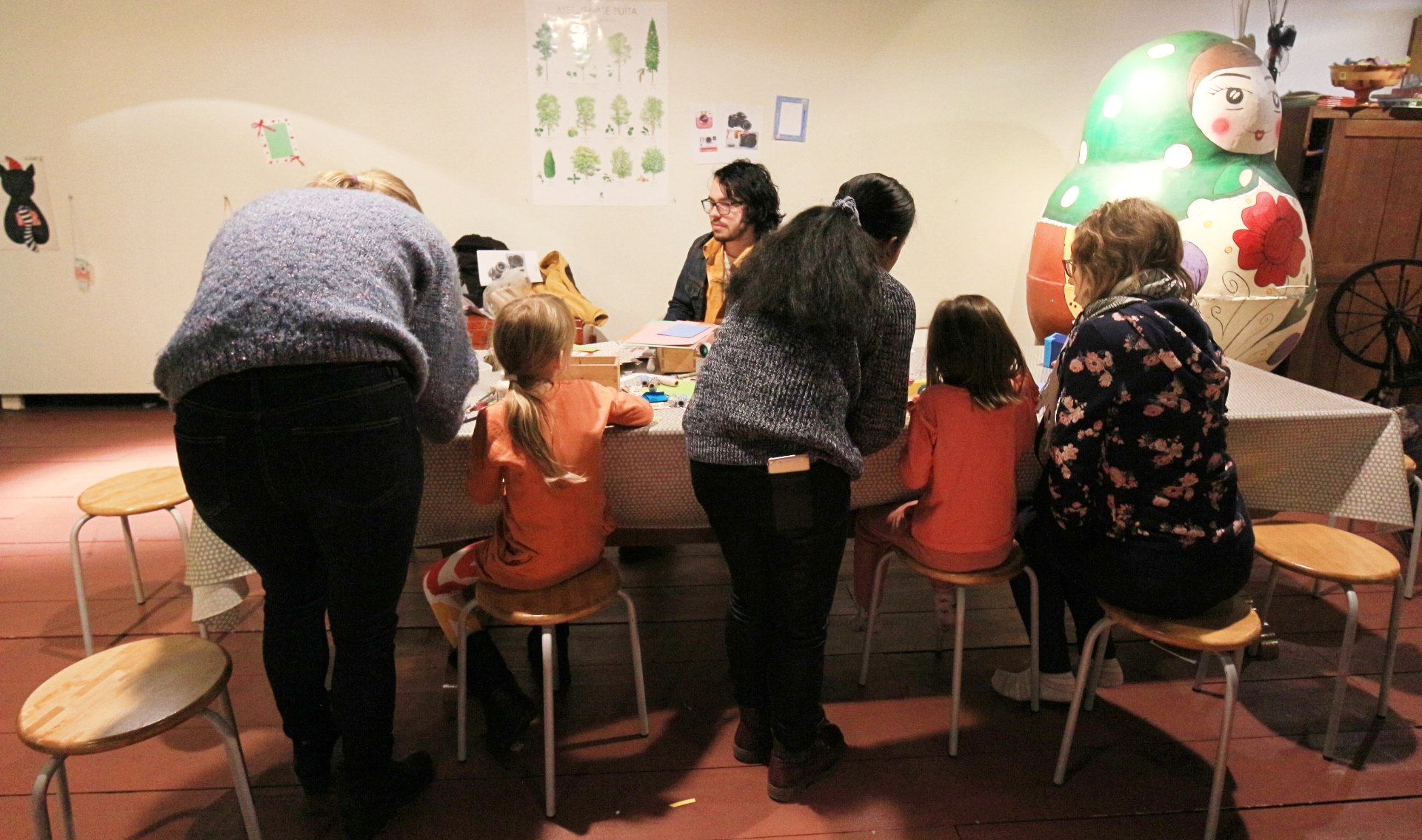 children and adults sit around a table making crafts.